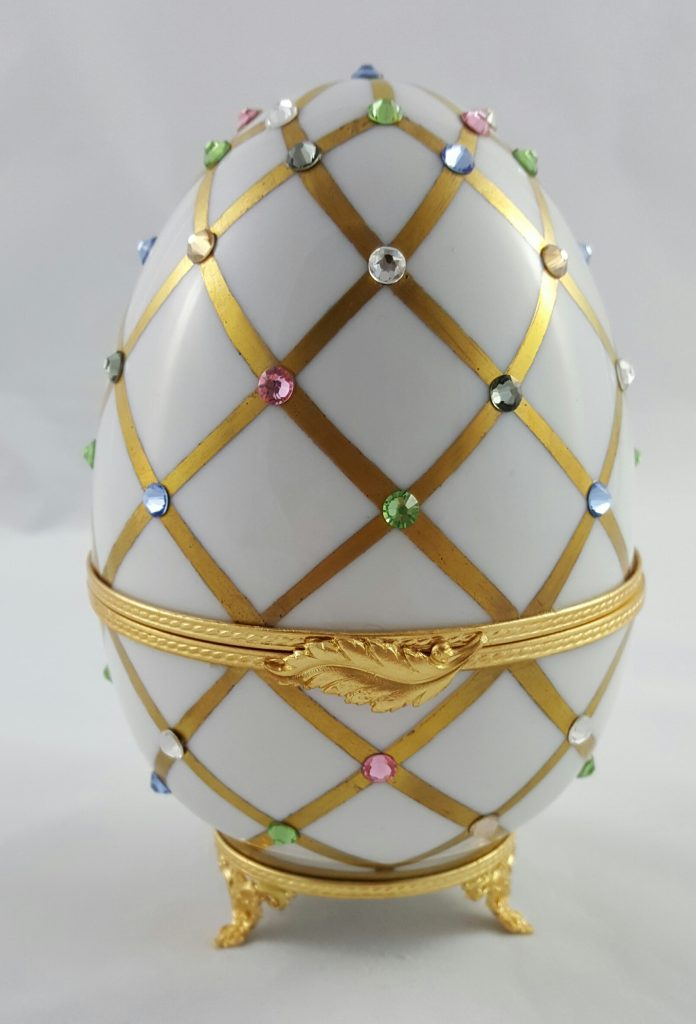 Oeuf treillis or mat et cristaux Swarovski comportant une figurine Swarovski